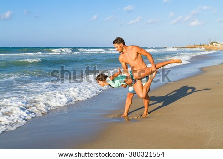 Athletic young couple does fitness exercises at the beach.