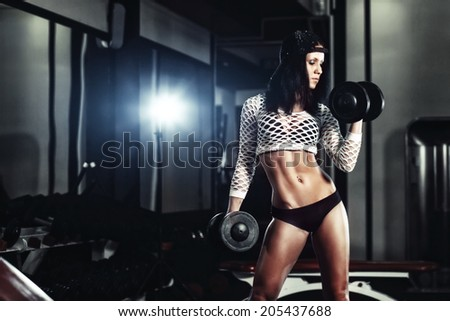 athletic young fitness girl doing a workout with dumbbells in the gym  - stock photo