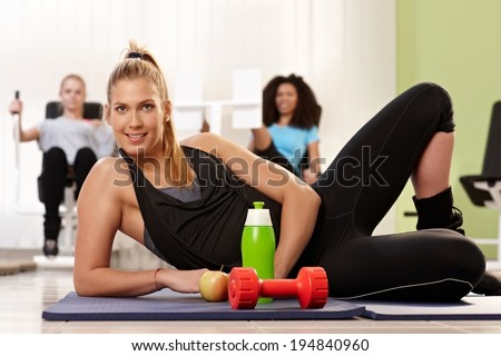 Athletic young girl lying on floor at the gym, having water, apple and dumbbell. - stock photo