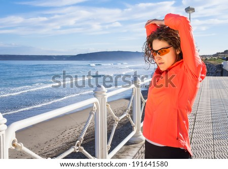 Athletic young girl warming before running in the beach promenade on a summer morning over blue cloudy sky background