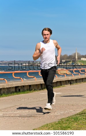 Athletic young male running on the shoreline - stock photo