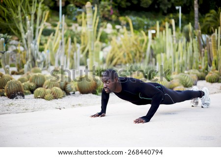 Athletic young man doing press ups before going for a run - stock photo