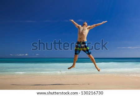Athletic young man enjoying the summer, jumping in a tropical beach - stock photo