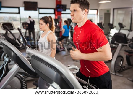 Athletic young man focused on his running and listening to music from his smartphone - stock photo