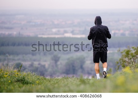 Athletic young man running during autumn, winter morning. Healthy lifestyle
