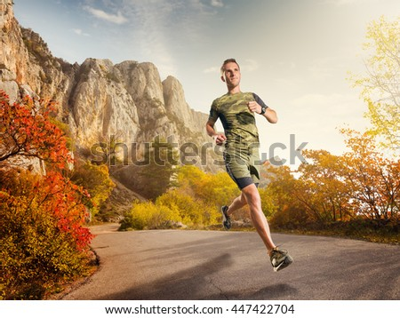 Athletic young man running in the nature on the mountains road. Runner jogging of beautiful scenery.  Healthy lifestyle.