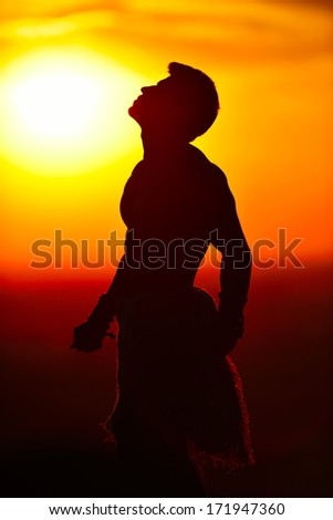 athletic young man silhouette outdoor at sunset - stock photo