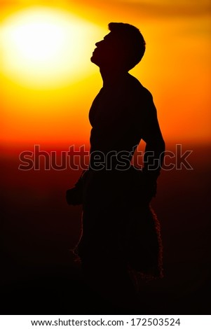 athletic young man silhouette outdoor at sunset