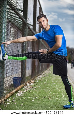 Athletic young man stretching for running in the nature. Healthy lifestyle