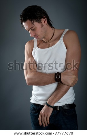 Athletic young man wearing jeans and white singlet against dark background. - stock photo