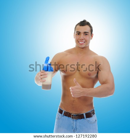 athletic young man with protein shake bottle. on blue background - stock photo