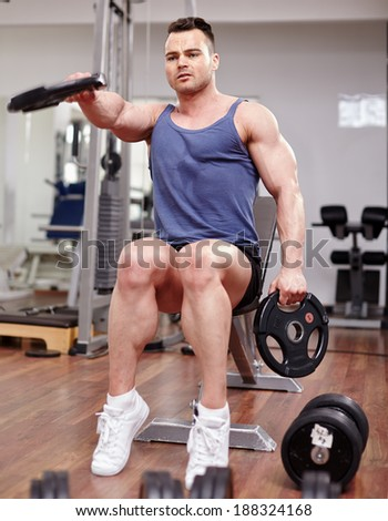 Athletic young man working with dumbbells in a modern gym - stock photo