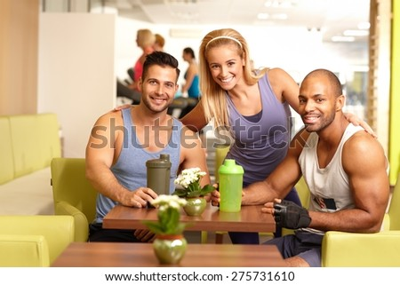 Athletic young people in gym bar, smiling, drinking refreshment, looking at camera. - stock photo