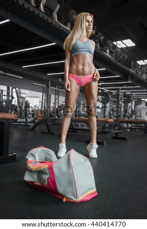 Athletic young sexy blonde girl prepares for exercising in the gym