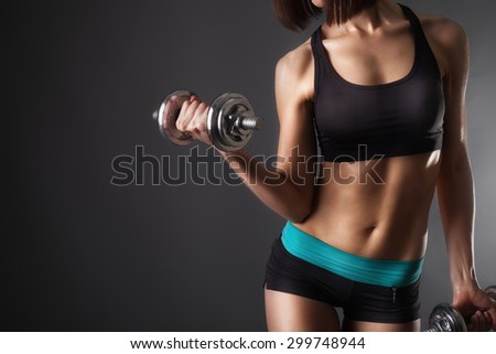 athletic young woman doing a fitness workout with dumbbells on black studio background