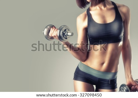 athletic young woman doing a fitness workout with dumbbells on gray studio background. High resolution  - stock photo
