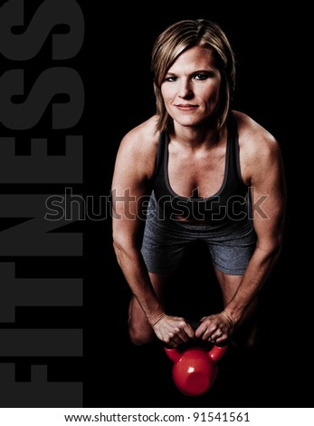 Athletic young woman doing a fitness workout with Kettlebell weights text space to the left - stock photo