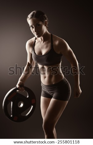 Athletic young woman doing exercise with barbell plate. Fitness sports. Healthcare, bodycare. - stock photo