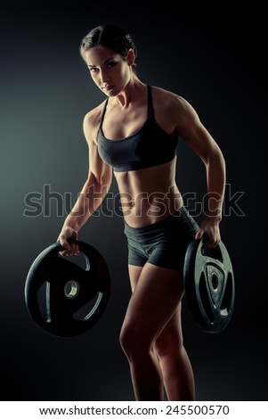 Athletic young woman doing exercise with barbell plates. Fitness sports. Healthcare, bodycare. - stock photo