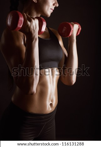Athletic young woman doing workout with weights on dark background - stock photo