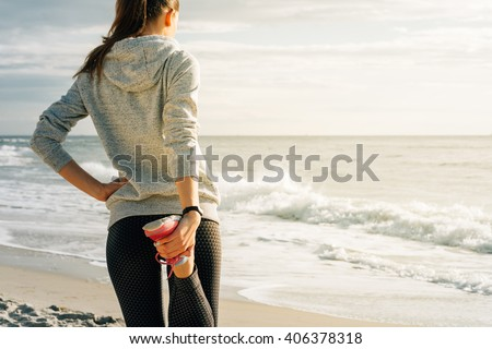 Athletic young woman engaged in morning exercises on the beach during sunrise, view from the back. The concept of a Healthy lifestyle. - stock photo
