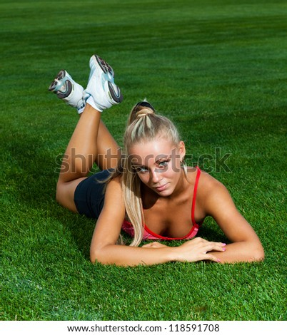 Athletic young woman in a sports suit lying on a green soccer field at the stadium - stock photo