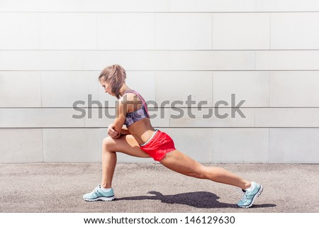 Athletic young woman in sports dress doing fitness exercise - stock photo