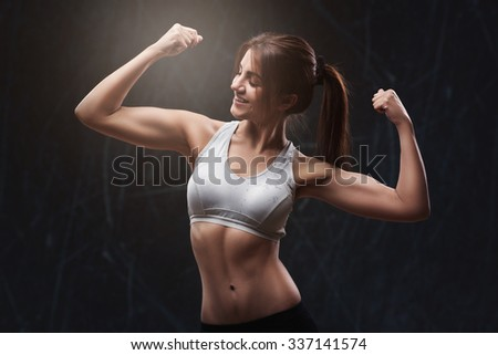 Athletic young woman isolated over dark grunge background - stock photo