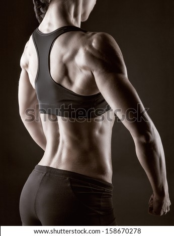 Athletic young woman showing muscles of the back and hands on a black background - stock photo