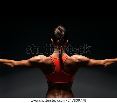 Athletic young woman showing muscles of the back and hands on a black background