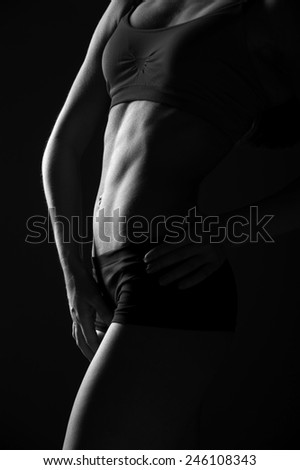 Athletic young woman with beautiful abdominal muscles on dark background. black and whites photo