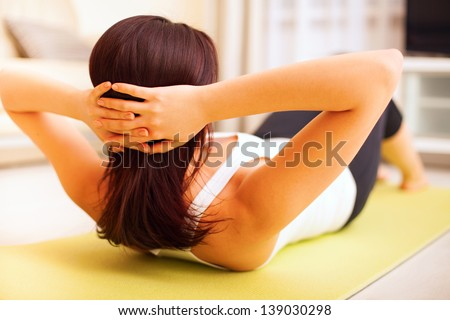 Athletic young woman working out at home lying on a mat doing liftups