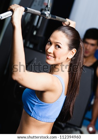 Athletic young woman works out on simulator in fitness gym - stock photo