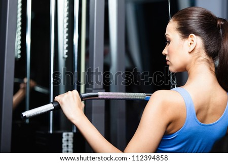 Athletic young woman works out on training apparatus in fitness gym - stock photo