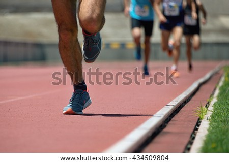 Athletics people running on the track field - stock photo