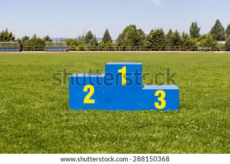 Athletics podium on grass - stock photo
