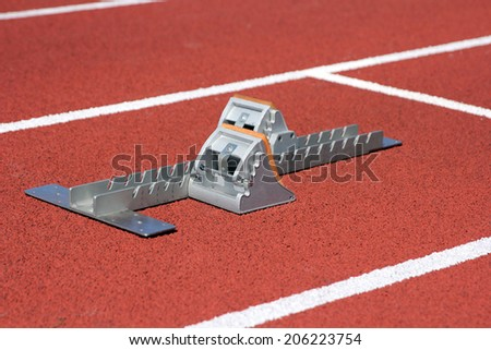 Athletics starting blocks on race track - stock photo