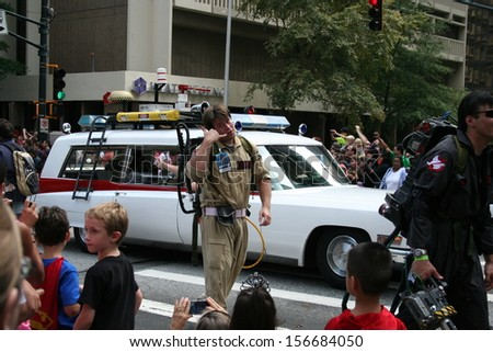 """ATLANTA - AUGUST 31: A replica Ghostbusters' car and someone dressed as a Ghostbuster signaling """"Who ya gonna call?"""" appear at the annual DragonCon parade August 31, 2013 in Atlanta. - stock photo"""