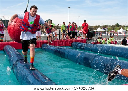 ATLANTA, GA - APRIL 5:  A man sprints across a narrow pipe trying to run through the wrecking balls event, at the Ridiculous Obstacle Challenge (ROC) 5K race, on April 5, 2014 in Atlanta, GA.  - stock photo