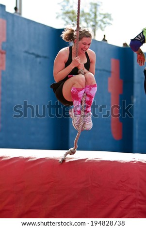 ATLANTA, GA - APRIL 5:  A young woman swings a rope across an obstacle in one of the events at the Ridiculous Obstacle Challenge (ROC) 5K race, on April 5, 2014 in Atlanta, GA.  - stock photo