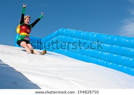 ATLANTA, GA - APRIL 5:  A young woman wearing a Robin superhero costume enjoys sliding down a  plastic slide in the Ridiculous Obstacle Challenge (ROC) 5K race, on April 5, 2014 in Atlanta, GA.  - stock photo