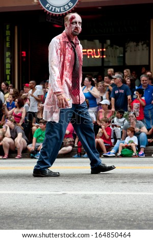 ATLANTA, GA - AUGUST 31:  A bloody zombie doctor menaces the crowd watching the Dragon Con parade pass by on Peachtree Street on August 31, 2013 in Atlanta, GA.  - stock photo