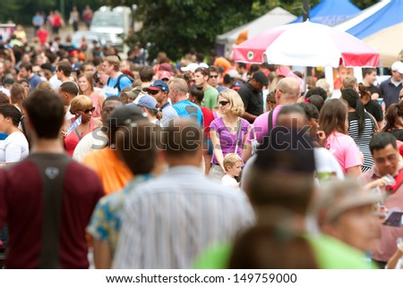 ATLANTA, GA - JULY 27:  A huge crowd gathers in Piedmont Park for the 3rd annual Atlanta Ice Cream Festival, on July 27, 2013 in Atlanta.   The event was free and open to the public.  - stock photo