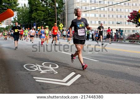 ATLANTA, GA - JULY 4:  A senior woman runs toward the finish line in the Peachtree Road Race on Independence Day, on July 4, 2014 in Atlanta, GA.  - stock photo