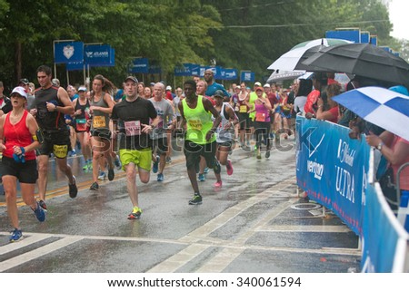ATLANTA, GA - JULY 4: Exhausted runners approach the finish line in the rain at the 46th running of the Peachtree Road Race 10K on July 4, 2015 in Atlanta, GA.  - stock photo