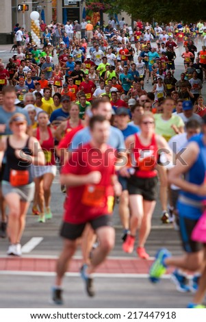 ATLANTA, GA - JULY 4: Thousands of runners make their way down Peachtree Street on their way to the finish line of the Peachtree Road Race on July 4, 2014 in Atlanta, GA.  - stock photo