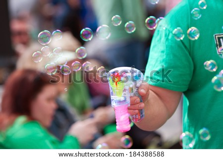 ATLANTA, GA - MARCH 15:  A man uses a bubble gun to blow bubbles at the St. Patrick's Day parade on Peachtree Street, on March 15, 2014 in Atlanta, GA.  - stock photo