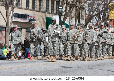 ATLANTA, GA - MARCH 15:  An army band walks and performs in the annual St. Patrick's parade on Peachtree St., on March 15, 2014 in Atlanta, GA.  - stock photo