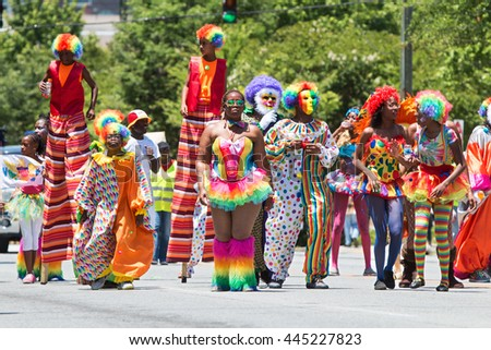 ATLANTA, GA - MAY 28: People wearing colorful clown costumes and walking on stilts participate in a parade celebrating Caribbean culture on North Avenue on May 28, 2016 in Atlanta, GA.