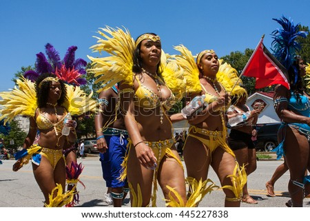 ATLANTA, GA - MAY 28:   Women wearing yellow bikinis and elaborate feathered costumes walk in a parade to celebrate Caribbean culture on North Avenue on May 28, 2016 in Atlanta, GA.